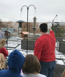 Here Innovations teacher, Mark Engle, shows Ready to Code participants where the bird feeders are located on the rooftop garden of Mifflin Park Elementary School.