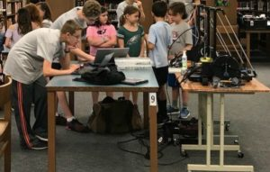 Student engineers show clients how to design an object on the 3D printers at the Feathered Friends Product Show. The engineers used 3D printers to design parts for the motion-sensing camera mounted near bird feeders.