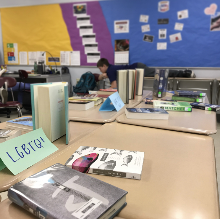 Books in foreground displayed in a classroom. The theme was identity, and the books pictured relate to LGBTQ+ themes. In the background, a student is reading comfortably.