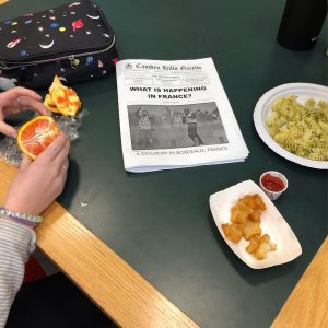 Photo depicts a student eating lunch in the library, with the school's literary newspaper nearby