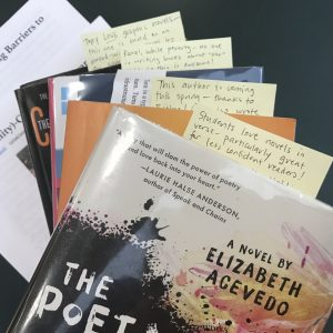 A stack of books, with annotations on sticky notes in each title