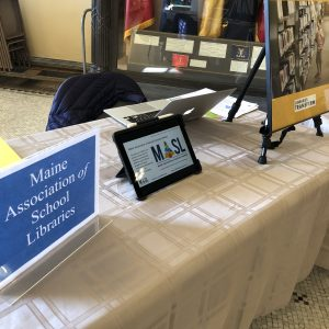 Table with sign for Maine Association of School Libraries, as well as an iPad showing our mission statement