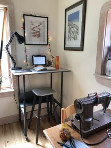 In the foreground, a low table with a sewing machine on it. In the background, a standing desk workspace.