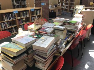 A table depicting many piles of books, returned after spring semester
