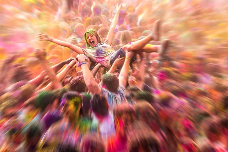 Joyful woman crowd surfing at a color festival