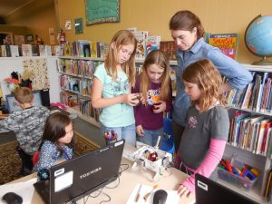 Vanessa Delgadillo, Greenleigh Harden, Emma O'Connor, North Central Regional Library Adult Services Manager Kim Neher and Audrey Schoenberg watch an EggBot draw a design on a Christmas ornament during the Mobile Makerspace event May 14 at the Waterville Library. (Karen Larsen photo)