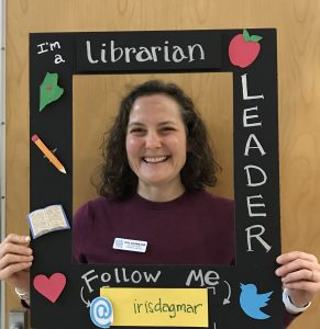 Librarian-Leader Iris Eichenlaub holds up a frame around her face with the words: I'm a Librarian-Leader, Follow Me: @irisdagmar
