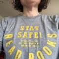 A selfie of a tee shirt that says: Stay Safe! Read Books!