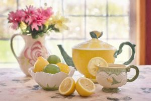 tea pot with bowl of lemons and tea cups