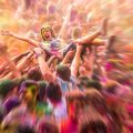 Joyful woman crowd surfing at a color festival
